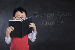 Male student reads book in classroom. Little boy reading a book while wearing glasses and uniform with text Do You Speak English on the chalkboard Royalty Free Stock Photos