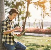 A male student relaxing and listening music seated on a grass in the city park.  royalty free stock images