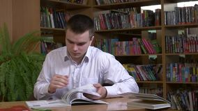 Male student researching with a book in a library stock video footage