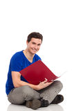 Male student with ring binder sitting on floor. Happy male student sitting on floor with red ring binder. Full length studio shot isolated on white Stock Photography