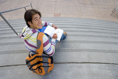 Male student with rucksack studying on steps, smiling, portrait, elevated view Royalty Free Stock Images