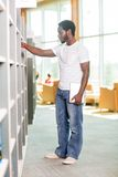 Male Student Selecting Book In Bookstore. Full length of male student with digital tablet selecting book in bookstore Royalty Free Stock Image
