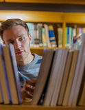 Male student selecting book in the library Royalty Free Stock Images