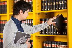 Male Student Selecting Book In Library. Young male student selecting book from shelf in library Stock Photography