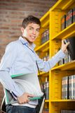 Male Student Selecting Book From Shelf In Library. Portrait of happy male student selecting book from shelf in college library Stock Photo