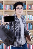 Male student showing a smartphone in the library Royalty Free Stock Images