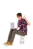 Male student showing thumbs up. Student sitting on stack of books Stock Photos
