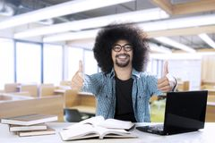 Male student showing thumbs up at the camera. Image of a male college student is learning with a laptop and books while showing thumbs up at the camera Royalty Free Stock Photo