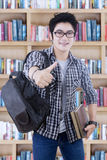 Male student shows thumbs up in the library. Image of clever male student showing thumb up while standing in the library Stock Photos