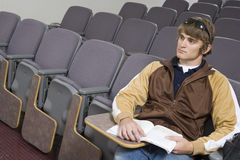 Male Student Sitting In Empty Classroom. Young male student with book in an empty classroom Stock Photography