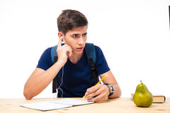 Male student sitting on exam with headphones. Male student sitting at the desk on exam with headphones isolated on a white background Royalty Free Stock Photos