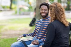 Male Student Sitting With Female Friend On Campus. Portrait of confident male student sitting with female friend on university campus Royalty Free Stock Photo
