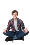 Male student sitting on the floor. Happy young male student sitting on the floor Royalty Free Stock Photography