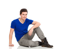 Male student sitting on the floor. Young man sitting on the floor. Full length studio shot isolated on white Stock Images