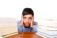 Male student sitting frustrated between books. Young handsome student sitting on a desk between study books and looks frustrated. Isolated on white Stock Images