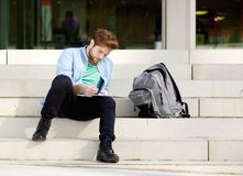 Male student sitting outside on campus reading notes Stock Images