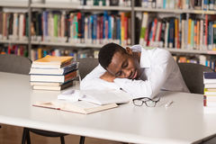 Male Student Sleeping In Library. Sleeping African Student Sitting And Leaning On Pile Of Books In College - Shallow Depth Of Field Royalty Free Stock Photo
