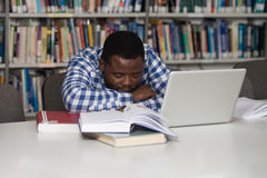 Male Student Sleeping In Library. Sleeping African Student Sitting And Leaning On Pile Of Books In College - Shallow Depth Of Field Royalty Free Stock Images