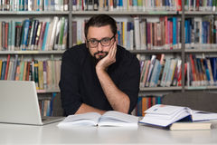 Male Student Sleeping In Library. Sleeping Caucasian Student Sitting And Leaning On Pile Of Books In College - Shallow Depth Of Field Royalty Free Stock Image