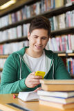 Male student with smartphone texting in library. People, education, technology and school concept - male student with smartphone and books texting message or Stock Photos