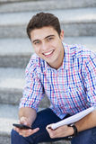 Male student smiling. Male student with mobile phone and notebook Stock Photo