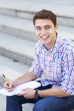 Male student smiling. Male student with pen and notebook Stock Photos