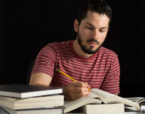 Male student solving exercise. Young man taking notes or solving exercise in a book Royalty Free Stock Images
