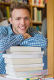 Male student with stack of books at library. Close up portrait of a smiling male student with stack of books at the college library Stock Photo