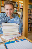 Male student with stack of books while others in background at library. Portrait of a smiling male student with stack of books while others in background at the Stock Photo