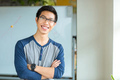 Male student standing with arms folded in university. Portrait of a happy asian male student standing with arms folded in university Royalty Free Stock Image
