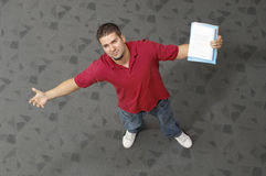 Male Student Standing With Arms Outstretched. High angle view of a young male student standing with arms outstretched Royalty Free Stock Photos