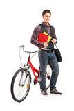 Male student standing by a bicycle. Full length portrait of a male student standing by a bicycle isolated on white background Stock Photo