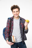 Male student standing with books and apple. Young happy male student standing with books and apple Stock Images