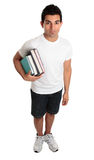 Male  student standing books under arm. Full length college or university student stands with some textbooks under one arm.   He is looking up with a neutral Royalty Free Stock Images