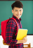 Male student standing in  classroom. Smiling male student standing in  classroom Royalty Free Stock Images