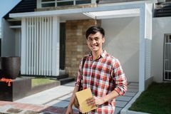 Male student standing in front of his house. Portrait of male student standing in front of his house stock images