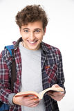 Male student standing with opened book. Happy male student standing with opened book over gray background Royalty Free Stock Photos