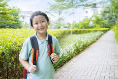 Male student standing on the park. Portrait of little boy smiling on the camera while carrying backpack, shot on the park Royalty Free Stock Photography