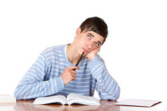Male student with study books looks contemplative. Young student is sitting on desk with open book and looks contemplative up.  Isolated on white Royalty Free Stock Photo