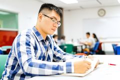 Male student study in the campus | Concentrate in doing homework. And writing down to notebook Royalty Free Stock Images