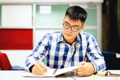 Male student study in the campus | Concentrate in doing homework. And writing down to notebook Royalty Free Stock Photo