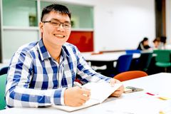 Male student study in the campus | Smiling and doing homework. By writing to the notebook Stock Images