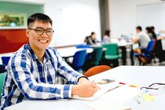 Male student study in the campus | Smiling and doing homework. By writing to the notebook Stock Photos