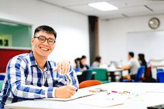 Male student study in the campus | Smiling and doing homework. By writing to the notebook Stock Photography