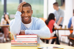 Male Student Studying In Classroom With Books. With Hand On Head Royalty Free Stock Image
