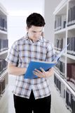 Male student studying in a library. Asian male student reading a book studying in a library Royalty Free Stock Photography
