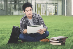 Male student with tablet in the campus yard Royalty Free Stock Images