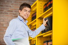 Male Student Taking Book From Shelf In Library. Portrait of confident male student taking book from shelf in library Royalty Free Stock Image
