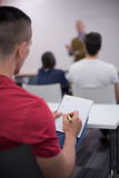 Male student taking notes in classroom Stock Photo