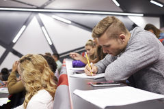 Male student taking notes in a university lecture theatre Royalty Free Stock Photos